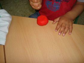 mano de niño aplastando una bola de plastilina roja