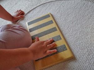 Imagen de un bebé jugando con las tablillas de tacto. Usando la tablilla con las lijas degradadas.