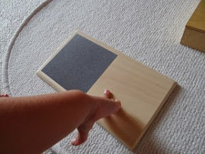 Imagen de niño jugando con la tablilla de tacto rugoso-suave.