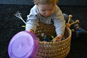 Imagen de bebé explorando una cesta del tesoro