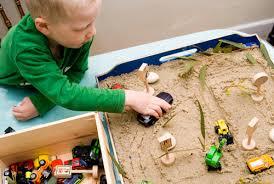 Fotografía de un niño jugando de forma libre con la bandeja de arena. Juego simbólico utilizando sus propios juguetes.