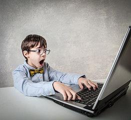Imagen de un niño que está investigando en Internet y realiza un descubrimiento que le impacta. Expresión facial de sorpresa.
