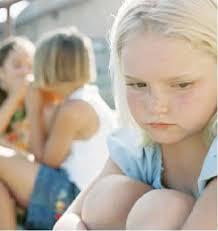 Imagen de una niña tímida apartada de un grupo de chicas que están jugando y divirtiéndose.