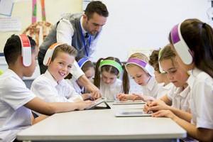 Fotografía de grupo de estudio utilizando las nuevas tecnologías. Profesor orientando a los alumnos.