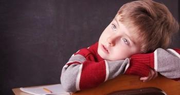 Fotografía de un niño distraído con tdah delante de los deberes.