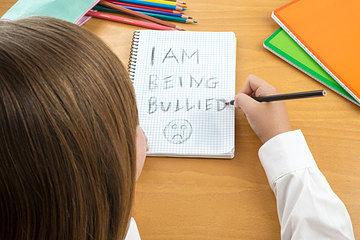 niña escribiendo en cuaderno que es acosada