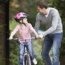 Padre enseñando a montar en bicicleta a su hija.